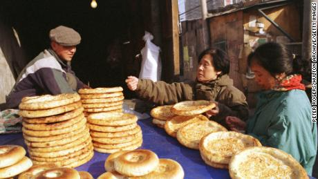 A Uyghur man sells traditional flat bread to women shoppers along Beijing's Xinjiang Street in 1999.