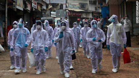 Health workers arrive at a medical camp in a slum in Mumbai, India on June 28