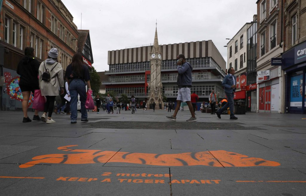 Shoppers walk past a social distancing message painted on the pavement in Leicester, England, on Monday, June 29.