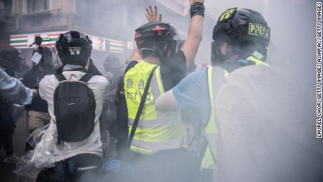 A journalist raises his hands after police fire tear gas on October 1, 2019 in Hong Kong. Pressure has been growing on reporters in the city under a new security law.
