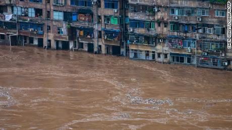 Floodwaters flow past a residential building in Chongqing in southwest China on July 1.