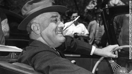 With a cigarette in a holder clenched in his teeth, a smiling Franklin Delano Roosevelt sits jauntily at the wheel of his convertible, Warm Springs, Georgia, 1939. (Photo by Underwood Archives/Getty Images)