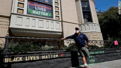 James Juanillo poses with a chalk message written outside of his home in San Francisco, California on June 14, 2020.