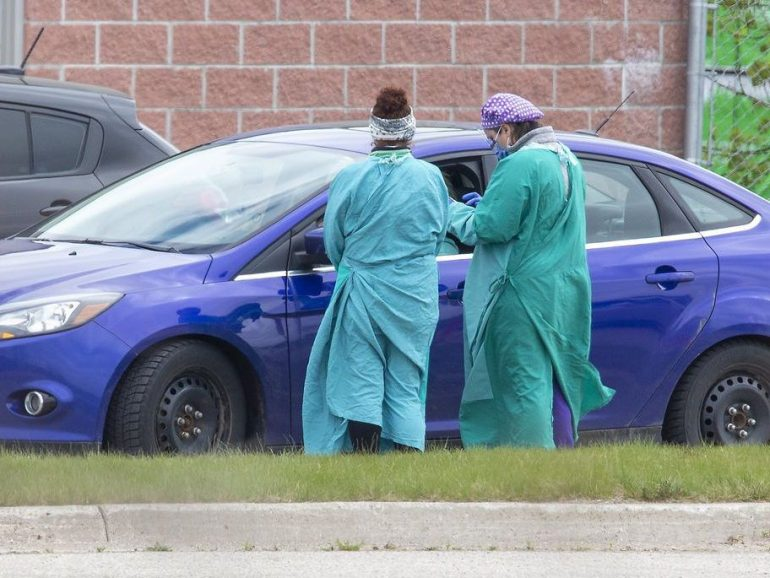 Health care workers assess a person at the Carling Heights Optimist Community Centre COVID-19 assessment centre  in London, Ont. on Monday May 4, 2020. Derek Ruttan/The London Free Press/Postmedia Network