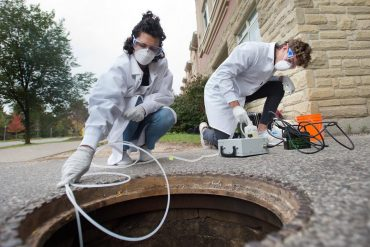 University of Guelph engineering students Melissa Novacefski, left, and Jonathan Evans, pump wastewater from a sewer outside a student residence on campus in late September to test for traces of COVID-19 RNA. Similar studies are being conducted in other cities, including Toronto.