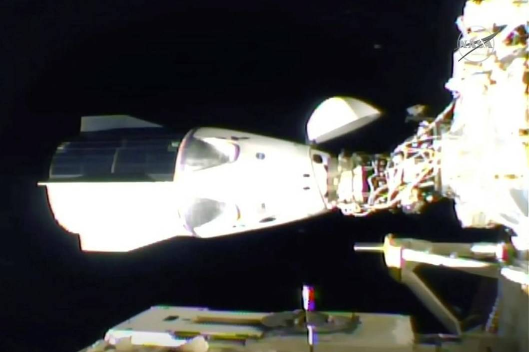 In this frame grab from NASA TV, the SpaceX Dragon is seen after docking at the International Space Station, late Monday, Nov. 16, 2020. (NASA TV via AP)