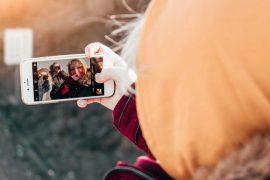 Eien Frau schaut auf ihr Smartphone und fotografiert sich und Freunde, die zurück fotografieren.