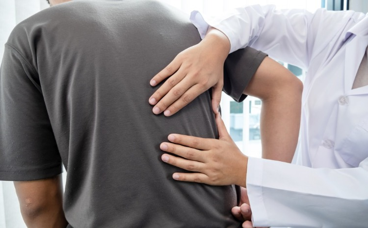 Male patient with back pain is treated by a specialist