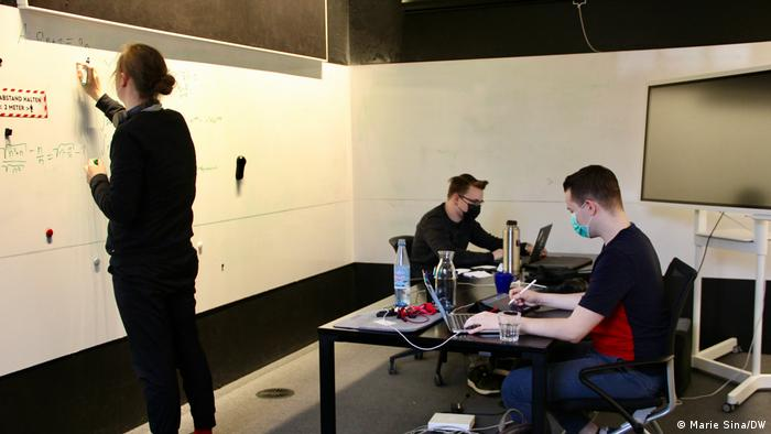 Three founders work on computers and a writing board