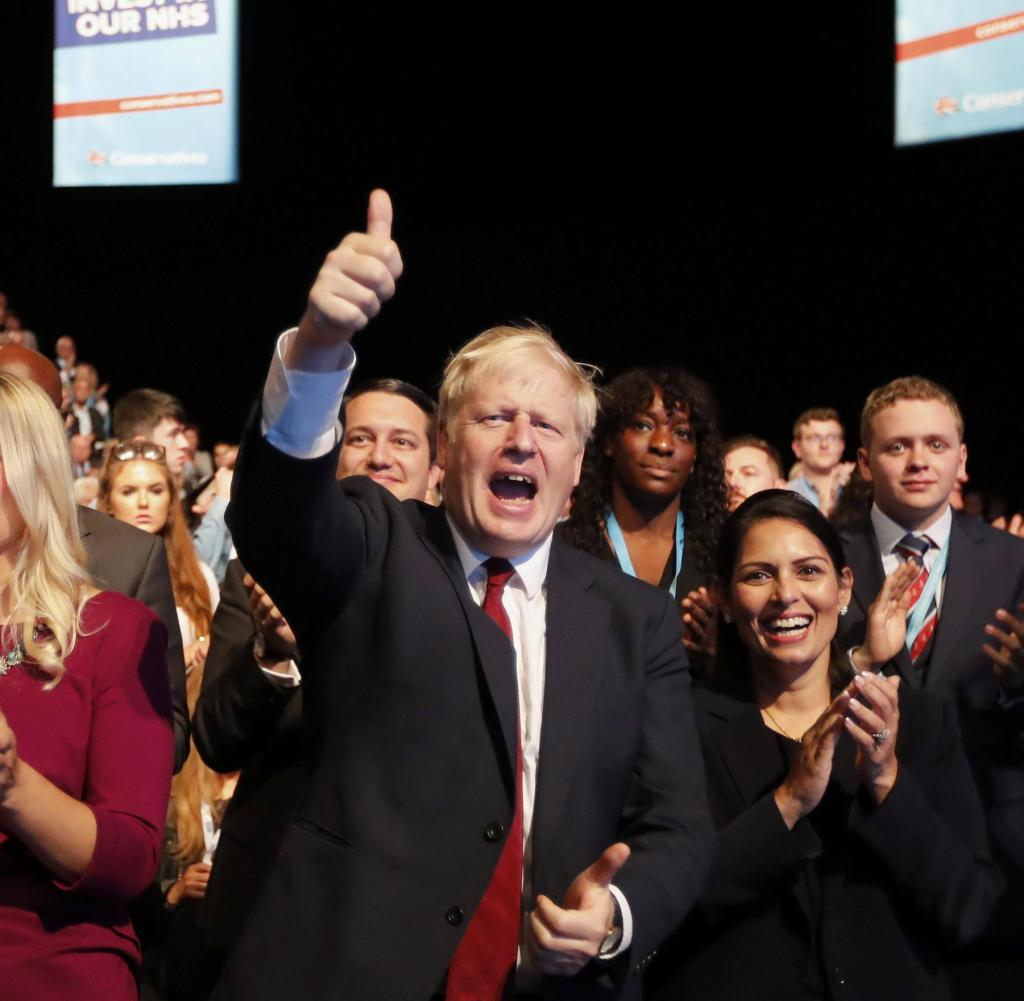 The Prime Minister of Great Britain, Boris Johnson (M), Priti Patel (R), Secretary of the Interior of Great Britain, sit in the convention center during the British Conservative Conference and hold their thumbs after a speech by the UK Treasury.  Secretary Javid.  +++ dpa-Bildfunk +++