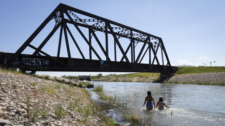 Kanada, Chestermere: Junge Leute kühlen sich in einem Bewässerungskanal ab. Die anhaltende Hitzewelle im Westen Kanadas hat für neue Höchsttemperaturen gesorgt und zu mehreren Todesfällen beigetragen. (Jeff Mcintosh/The Canadian Press/AP)
