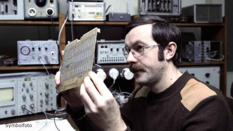 An engineer looks at an electronic component.