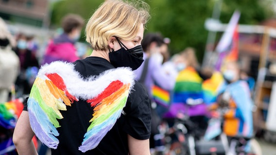 Participants stand with colored feathers on the Schützenplatz in Hanover as part of Lenia CSD (Christopher Street Day).  © dpa-buildfunk Photo: Hauke-Christian Ditricho